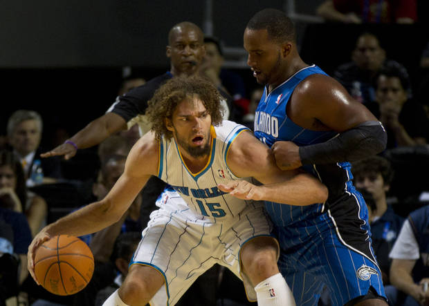 New Orleans Hornets' Robin Lopez (15) attempts to dribble past Orlando Magic Glen Davis during a NBA preseason basketball game in Mexico City on Saturday, Oct. 7, 2012. (AP Photo/Eduardo Verdugo)