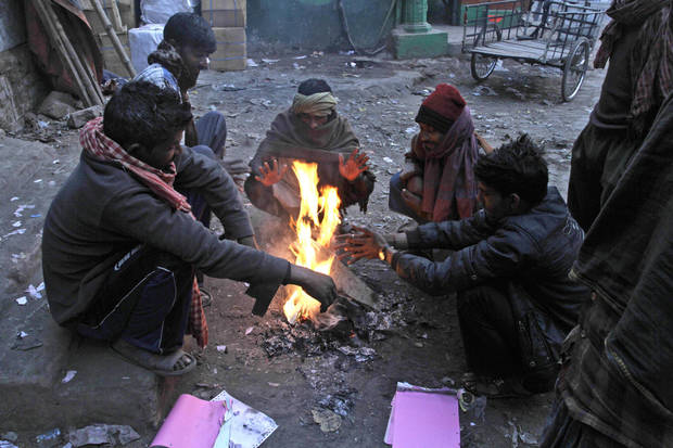 Indian laborers warm themselves around a bonfire on a cold winter morning in Kolkata, India, Friday, Jan. 11, 2013. More than 100 people have died of exposure as several parts of India deal with historically cold temperatures. (AP Photo/Bikas Das)
