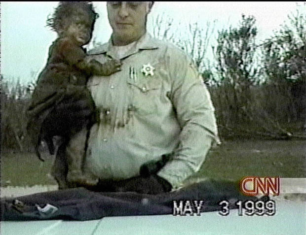 Tornado survivor: Aleah Crago is lifted onto the patrol car of Dep. Robert Jolley of the Grady Co. Sheriff's Dept. as shown in a video image taken Monday, May 3, 1999 after she was rescued from the tornado in Oklahoma.  (AP Photo/Grady Co. Sheriff via CNN) MANDATORY CREDIT: CNN