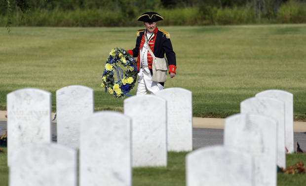 A member of the Sons of the American Revolution San Antonio Chapter carries a wreath to a Fourth of July Patriotic Ceremony at Fort Sam Houston National Cemetery, Thursday, July 4, 2013, in San Antonio. (AP Photo/Eric Gay)