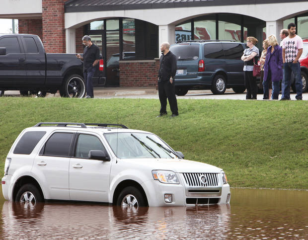 Victims of the high water and others look over the flooded vehicles Monday on Pennsylvania Avenue just south of Memorial Road.  PHOTO BY DAVID MCDANIEL, THE OKLAHOMAN