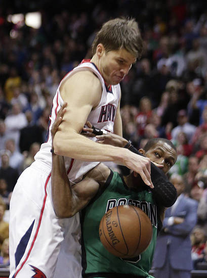 Atlanta Hawks guard Kyle Korver (26), left, works against Boston Celtics guard Rajon Rondo for the ball in the second of an NBA basketball game Friday, Jan. 25, 2013, in Atlanta. Atlanta won 123-111 in double-overtime. (AP Photo/John Bazemore)