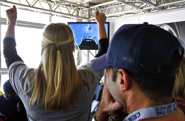 As project team members cheer on Felix Baumgartner, of Austria, he leaps out of the space capsule, as seen on television, at a height of just over 128,000 feet above the Earth's surface, Sunday, Oct. 14, 2012, in Roswell, N.M. Baumgartner came down safely in the eastern New Mexico desert minutes about nine minutes after jumping from his capsule 128,097 feet, or roughly 24 miles, above Earth.  (AP Photo/Ross D. Franklin) ORG XMIT: NMRF120