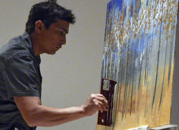 Artist Tony Abeyta works on an oil painting before a live audience Sunday at the Fred Jones Jr. Museum of Art as part of a celebration of the opening of the James T. Bialac Native American Art Collection.  PHOTO BY CONNIE HEFNER, FOR THE OKLAHOMAN