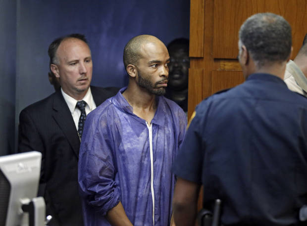 Michael Madison is brought into court for his arraignment in East Cleveland, Ohio on Monday, July 22, 2013. Madison is charged with aggravated murder in the deaths of three women found in garbage bags in the city. (AP Photo/Mark Duncan)