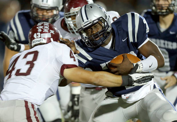 Edmond North's Michael Farmer fights off Grant Carro during a high school football playoff game at Wantland Stadium in Edmond, Okla., Thursday, Nov. 8, 2012. Photo by Bryan Terry, The Oklahoman