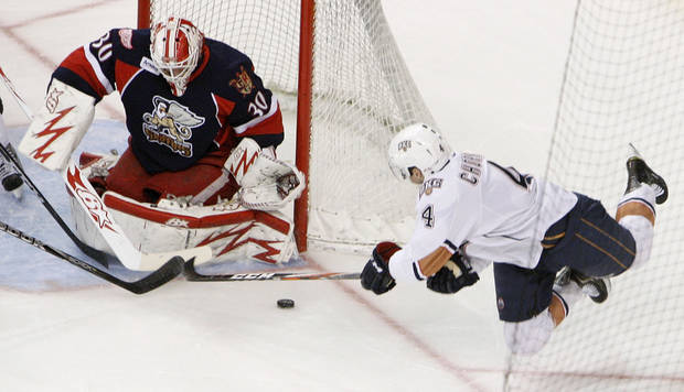 Oklahoma City's Taylor Chorney (4) tries to score on Grand Rapids' goalie Tom McCollum (30) during an AHL hockey game between the Oklahoma City Barons and the Grand Rapids Griffins at the Cox Convention Center in Oklahoma City, Saturday, March 24, 2012. Photo by Nate Billings, The Oklahoman