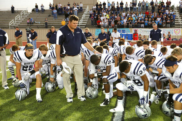 Edmond North coach Jeremy Dombek and his team bow their heads in a moment of silence to remember Ryan Smith before Friday's game against Westmoore. PHOTO BY STEVE SISNEY, THE OKLAHOMAN