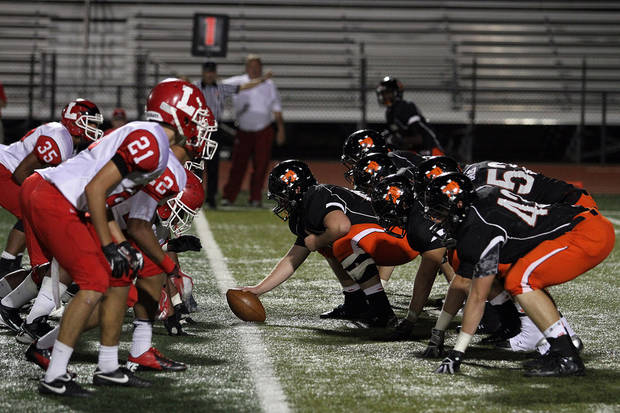 The Norman offensive line and the Lawton defense are ready for the snap during the Lawton - Norman High School football game at Harve Collins Field at Norman High School in Norman Friday night. PHOTO BY HUGH SCOTT FOR THE OKLAHOMAN ORG XMIT: KOD