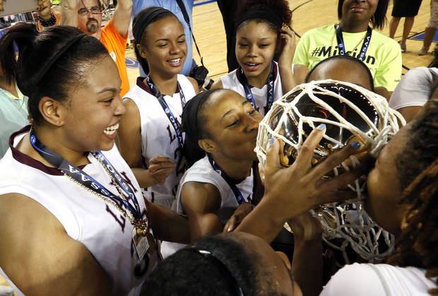 Teammates hold the gold championship ball and Latia Robertson gives it a kiss following the 2A girls championship game where the Northeast Academy Lady Vikings defeated the Alva high school Lady Bugs 53-36 at the State Fair Arena on Saturday, March 9, 2013 in Oklahoma City, Okla.  Photo by Steve Sisney, The Oklahoman