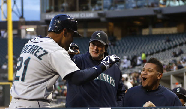 Seattle Mariners' Franklin Gutierrez (21) is greeted at the dugout after hitting a lead-off home run off Chicago White Sox starting pitcher Jose Quintana during the first inning of a baseball game on Friday, April 5, 2013, in Chicago. (AP Photo/Charles Rex Arbogast)