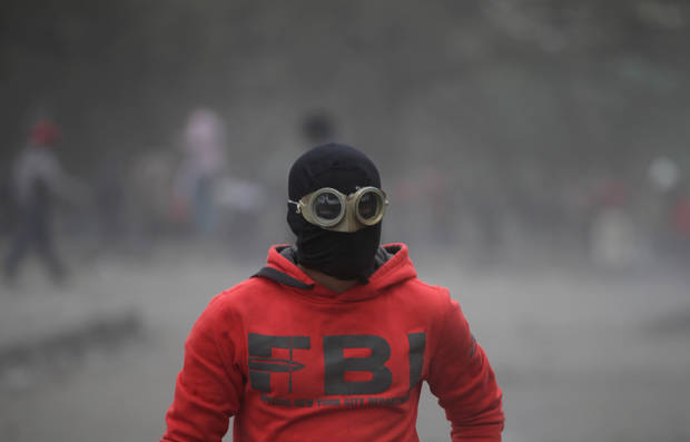 An Egyptian protester part of the Black Bloc, clashes with riot police, not seen, near Tahrir Square, Cairo, Egypt, Monday, Jan. 28, 2013. An unpredictable new element has entered Egypt�s wave of political unrest, a mysterious group of black-masked young men calling themselves the Black Bloc. They present themselves as the defenders of protesters against the rule of President Mohammed Morsi, but Islamists have used them to depict the opposition as a violent force wrecking the nation. (AP Photo/Khalil Hamra)
