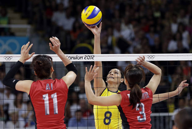 Brazil's Jaqueline Carvalho (8) spikes the ball between Japan's Ai Otomo (11) and Yoshie Takeshita (3) during a women's volleyball semifinal match at the 2012 Summer Olympics Thursday, Aug. 9, 2012, in London. (AP Photo/Chris O'Meara)