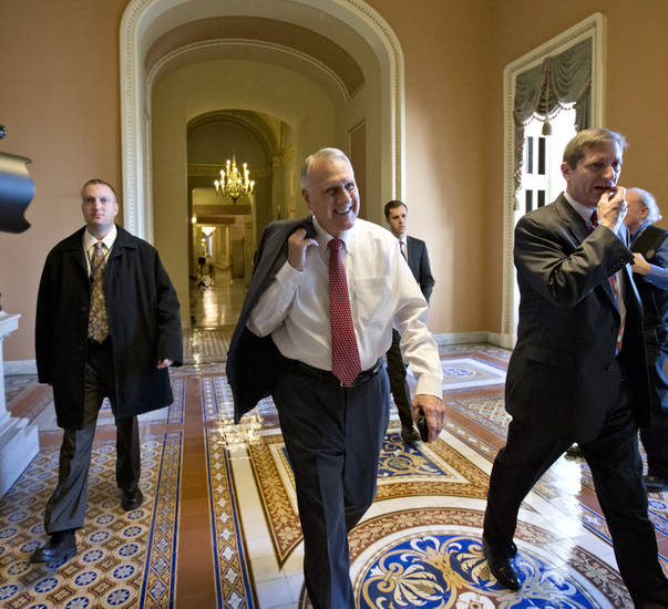"Senate Minority Whip Jon Kyl of Arizona walks between the Senate chamber and the office of Senate Minority Leader Mitch McConnell of Kentucky, as Democrats and Republicans try to negotiate a legislative path to avoid the so-called ""fiscal cliff,"" in Washington, Sunday, Dec. 30, 2012.   (AP Photo/J. Scott Applewhite)"
