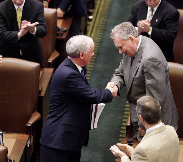 Gov. Frank Keating, left, shakes hands with Sen. Gene Stipe as Keating makes his way to the front of the House chambers to deliver his state of the state message to a joint session of the Oklahoma Legislature. FOR FILES