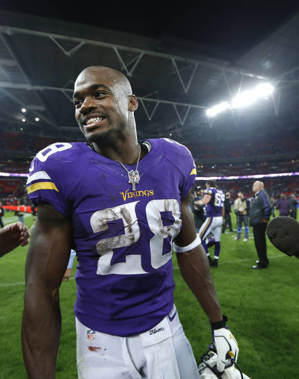 Minnesota Vikings running back Adrian Peterson smiles as he leaves the field at the end of the NFL football game against Pittsburgh Steelers at Wembley Stadium, London, Sunday, Sept. 29, 2013.  The Vikings won the match 34-27. (AP Photo/Sang Tan)