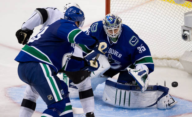 Vancouver Canucks goalie Cory Schneider, right, stops Los Angeles Kings&#039; Dustin Brown as Alexander Edler, of Sweden, defends during the third period of an NHL hockey game in Vancouver, British Columbia on Saturday, March 2, 2013. (AP Photo/The Canadian Press, Darryl Dyck)