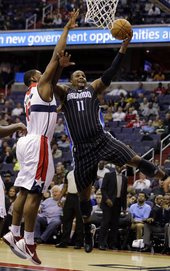 Orlando Magic forward Glen Davis (11) goes up for a shot as he guarded by Washington Wizards forward Kevin Seraphin (13) from France, in the first half of an NBA basketball game Monday, Jan. 14, 2013 in Washington. (AP Photo/Alex Brandon)