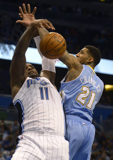 Orlando Magic center Glen Davis, left, and Denver Nuggets forward Wilson Chandler battle for a rebound during the first half of an NBA basketball game in Orlando, Fla., Friday, Nov. 2, 2012. (AP Photo/Phelan M. Ebenhack)