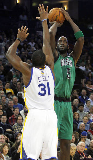 Boston Celtics' Kevin Garnett (5) shoots over Golden State Warriors' Festus Ezeli (31) during the first half of an NBA basketball game in Oakland, Calif., Saturday, Dec. 29, 2012. (AP Photo/George Nikitin)