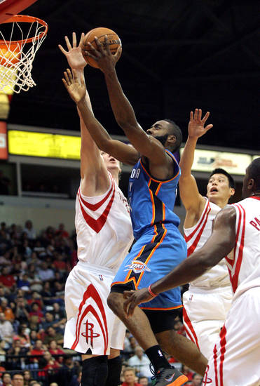Oklahoma City Thunder's James Harden, center, goes to the basket past Houston Rockets' Omar Asik, left, and Jeremy Lin during the second quarter of an NBA preseason basketball game in Hidalgo, Texas, Wednesday, Oct. 10, 2012. (AP Photo/Delcia Lopez) ORG XMIT: TXDL110