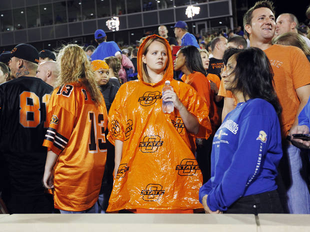 Ashley Davidson of Tulsa wears an OSU poncho as fans begin to leave the stadium to seek shelter from severe weather in the area before the Oklahoma State-Tulsa game on Saturday. Photo by Nate Billings, The Oklahoman