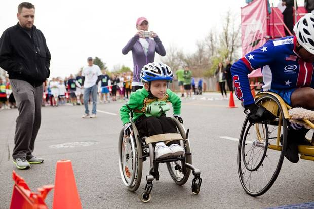 Four-year-old Ryder Gibson pushes off the starting line as mom Christi Gibson and father Brian Gibson look on at the wheelchair 5k of the Redbud Classic at Nichols Hills Plaza in Nichols Hills, OK, Sunday, April 6, 2014. Photo by KT King, The Oklahoman
