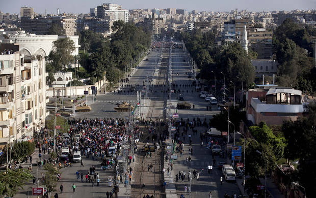 Egyptian army tanks secure the perimeter of the presidential palace while protesters gather chanting anti president Mohammed Morsi slogans, in Cairo, Egypt, Friday, Dec. 7, 2012. Thousands of Egyptians took to the streets after Friday midday prayers in rival rallies and marches across Cairo, as the standoff deepened over what opponents call the Islamist president's power grab, raising the specter of more violence. (AP Photo/Nasser Nasser)