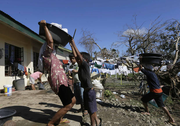 Typhoon evacuees prepare to do their laundry at an evacuation center at Maparat township, Compostela Valley in southern Philippines Saturday Dec. 8, 2012. Search and rescue operations following typhoon Bopha that killed nearly 600 people in the southern Philippines have been hampered in part because many residents of this ravaged farming community are too stunned to assist recovery efforts, an official said Saturday. (AP Photo/Bullit Marquez)