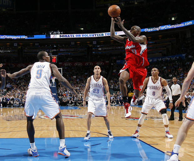 The Clippers Jamal Crawford (11) passes the ball between Oklahoma City's Serge Ibaka (9), Kevin Martin (23), and Russell Westbrook (0) during an NBA basketball game between the Oklahoma City Thunder and the Los Angeles Clippers at Chesapeake Energy Arena in Oklahoma City, Wednesday, Nov. 21, 2012. Photo by Bryan Terry, The Oklahoman