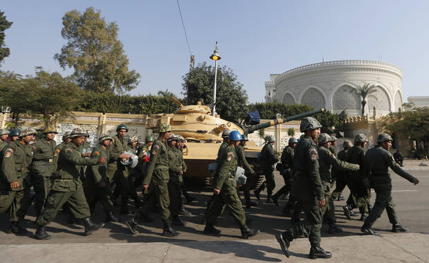 "Soldiers walk past a military tank securing the presidential palace in Cairo, Egypt, Thursday, Dec. 13, 2012. Egypt's opposition called on its followers to vote ""no"" in a crucial referendum on a disputed constitution drafted by Islamist supporters of President Mohammed Morsi. (AP Photo/Petr David Josek)"