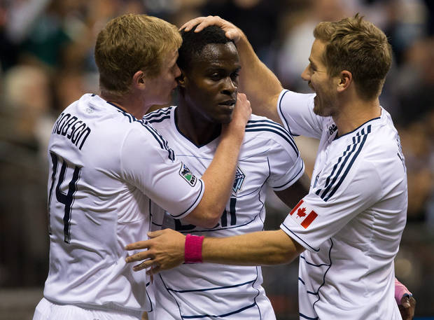 From left to right, Vancouver Whitecaps' Barry Robson, of Scotland, Gershon Koffie, of Ghana, and Jordan Harvey celebrate Koffie's goal against Chivas USA during the first half of an MLS soccer game in Vancouver, British Columbia, Wednesday, Oct. 3, 2012. (AP Photo/The Canadian Press, Darryl Dyck)