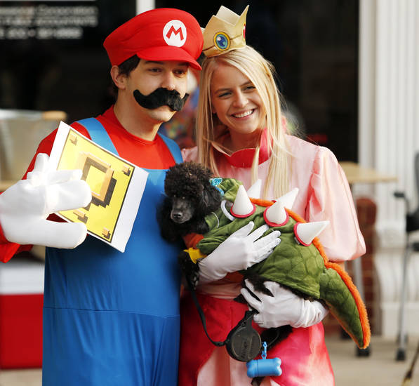 "Nick Crouch, ""Mario,"" Cassie Mongold, ""Princess Pear,"" and their dog Maeby, ""Bowser,"" pose for photographs at the first Fall Fest in downtown on Friday, Oct. 25, 2013 in Norman, Okla.  Photo by Steve Sisney, The Oklahoman"