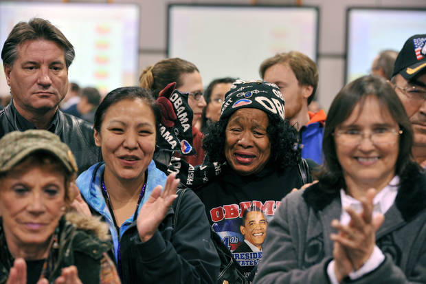 A crowd listens to a broadcast of President Barack Obama's victory speech Tuesday, Nov. 6, 2012, including Sheridan Williams, center, in Anchorage, Alaska. (AP Photo/Michael Dinneen)