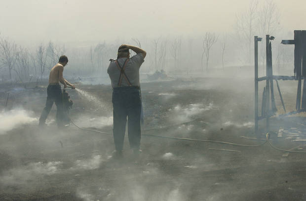 Homeowners battle grass fires in Midwest City, Thursday, April 9, 2009.  Photo by Jim Beckel, The Oklahoman