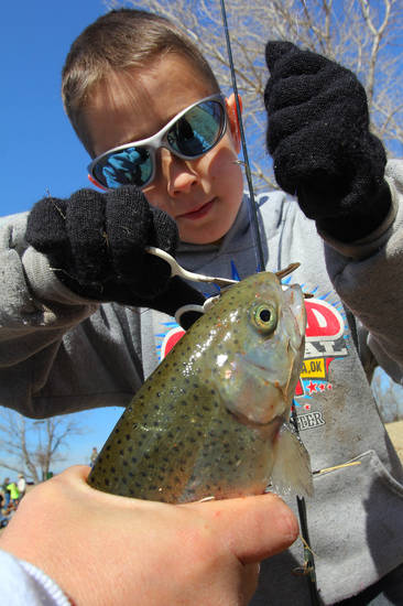 Hunter Ogden, 10, of Yukon cuts the line off his first catch of the day during the Trout Fish Out Saturday, March 2, 2013,  morning at the Dale Robertson Activity Center pond in Yukon. PHOTO BY HUGH SCOTT FOR THE OKLAHOMAN
