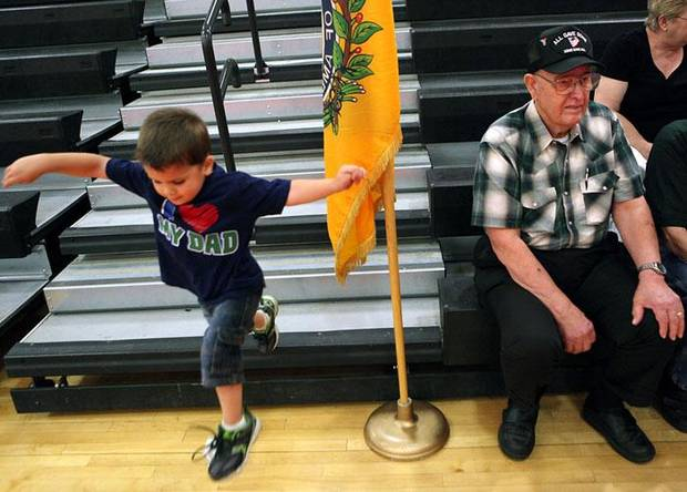 Russell Traut, age 3, plays on the bleachers inside Rinehart Fitness Center, while Billy Nash, (right) a member of Vietnam Veterans of America Chapter 751, waits for soldiers to arrive prior to a homecoming ceremony for soldiers returning from Iraq at Fort Sill on Tuesday, June 8, 2010. The Vietnam Veterans group, based in Lawton, Okla., have been to every deployment and homecoming since Sept. 11, 2001. Russell Traut and his family welcomed home Russell's father, SSgt. Michael Traut. Photo by John Clanton, The Oklahoman ORG XMIT: KOD