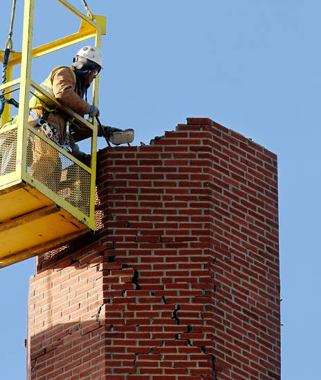 A man works from inside a basket attached to a crane to remove individual bricks from the southeast turret on Benedictine Hall. The four turrets atop the hall were damaged as a result of a 5.6-magnitude earthquake. File photo by Jim Beckel, The Oklahoman <strong>JIM BECKEL - THE OKLAHOMAN</strong>