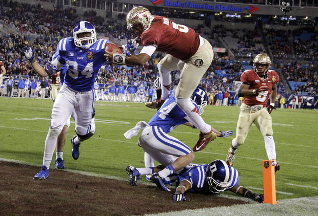 FILE - In this Dec. 7, 2013, file photo, Florida State's Jameis Winston (5) leaps over Duke's Bryon Fields (14) for a touchdown in the second half of the Atlantic Coast Conference Championship NCAA football game in Charlotte, N.C. Winston has the opportunity to accomplish what only one other player has achieved _ win consecutive Heisman trophies. Twenty-three underclassmen have won the award, but Ohio State running back Archie Griffin was the only one to pull off the feat. (AP Photo/Bob Leverone, File)