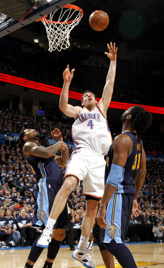 Oklahoma City's Nick Collison (4) goes to the basket between Denver's Wilson Chandler (21) and Nene (31) during the NBA basketball game between the Denver Nuggets and the Oklahoma City Thunder in the first round of the NBA playoffs at the Oklahoma City Arena, Wednesday, April 27, 2011. Photo by Bryan Terry, The Oklahoman