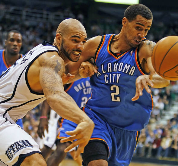 Oklahoma City Thunder's Thabo Sefolosha, right, fights for a ball with Utah Jazz's Carlos Boozer during the second half of an NBA basketball game in Salt Lake City, Saturday, Nov. 24, 2009. The Thunder beat the Jazz 104-94. (AP Photo/George Frey)