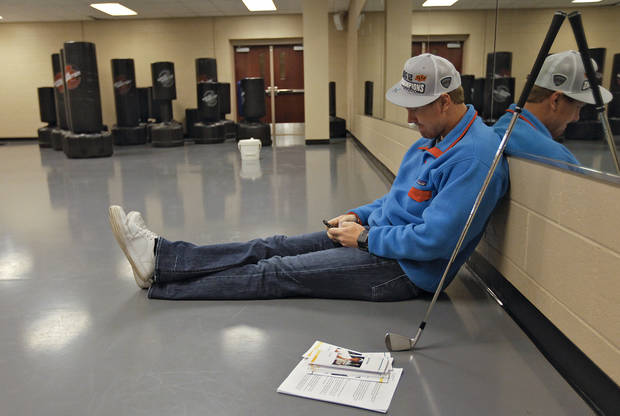 Oklahoma State quarterback Brandon Weeden relaxes on the floor while reading news on his cell phone before the start of his golf class at OSU's Colvin Center in Stillwater, Okla. on Thursday, Dec. 8, 2011. Photo by Chris Landsberger, The Oklahoman