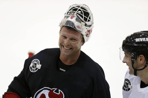 New Jersey Devils goalie Martin Brodeur, left, talks to left wing Mathieu Darche during the team's first official practice since the NHL hockey lockout ended, Sunday, Jan. 13, 2013, in Newark, N.J. (AP Photo/Julio Cortez)