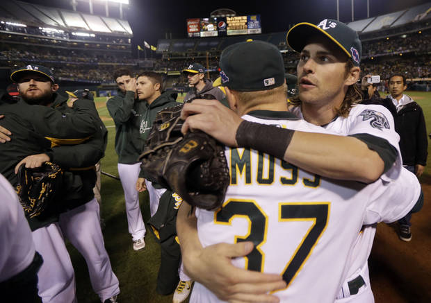 Oakland Athletics right fielder Brandon Moss hugs teammate Josh Reddick after the A's lost 6-0 to the Detroit Tigerts in Game 5 of an American League division baseball series in Oakland, Calif., Thursday, Oct. 11, 2012. (AP Photo/Marcio Jose Sanchez)