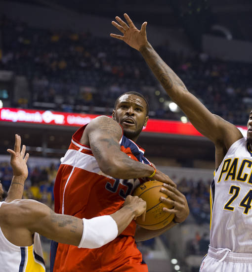 Washington Wizards power forward Trevor Booker (35) tries to maintain control of the ball as he drives the lane between Indiana Pacers David West, left, and Paul George (24) during first-half action in an NBA basketball game in Indianapolis, Saturday, Nov. 10, 2012. (AP Photo/Doug McSchooler)