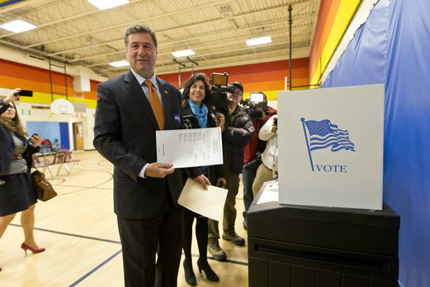 Virginia Republican senate candidate George Allen, joined by his wife Susan, holds up his ballot for reporters as they voted in their home precinct in the Mount Vernon area of Fairfax County, Va., Tuesday, Nov. 6, 2012. (AP Photo/J. Scott Applewhite)
