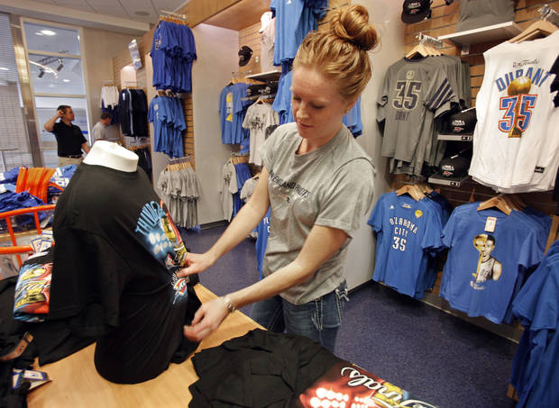 Thunder Shop retail operations manager Amy Lyon displays merchandise as the store opens at 8:30 a.m. on the day of the first game of the NBA basketball finals at the Chesapeake Arena on Tuesday, June 12, 2012 in Oklahoma City, Okla.  Photo by Steve Sisney, The Oklahoman