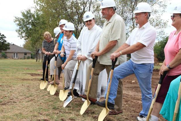 The Rev. Jack Feehily, center, smiles Sunday as he prepares to dig at the ceremonial groundbreaking for St. Andrew Catholic Church's new youth center in Moore. With Feehily are parish members. PHOTO BY THOMAS MAUPIN, THE OKLAHOMAN <strong>The Oklahoman - Thomas Maupin</strong>