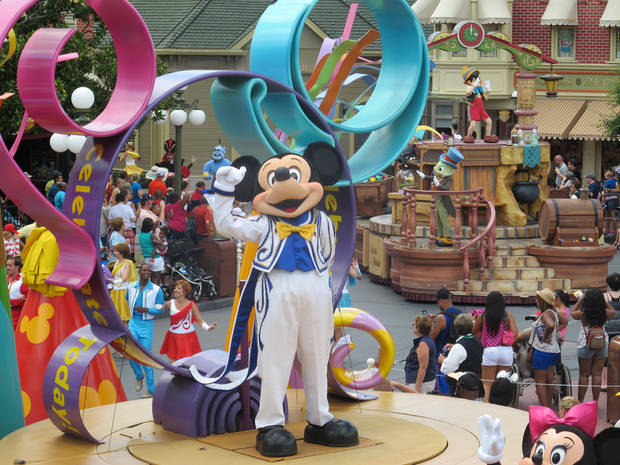 Mickey Mouse waves to parade goers in Disney�s Magic Kingdom theme park.  PHOTO BY Richard Hall, THE OKLAHOMAN