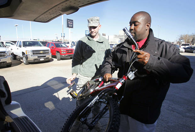 Luther Thompson assists Staff Sgt. Brittain Wright with his bicycle, which was donated.   Photo by PAUL HELLSTERN, The Oklahoman